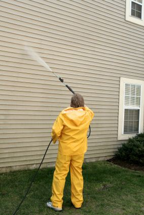 Pressure washing the siding of a house by Apex Facility Services, LLC.